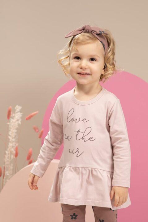 Mädchen trägt rosa Kinder Langarmshirt Oberteil in Kleidchen Optik Tunika mit Print LOVE IN THE AIR - Stirnband mit Schleife - Baby Leggings mit Blumen in Dunkelrosa von Pinokio - Kinderfoto Nahaufnahme