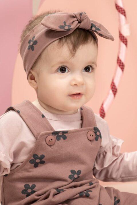 Mädchen trägt dunkelrosa Baby Latzhose Trägerhose mit Blumenmuster - Kinder Stirnband mit Schleife rotbraun - Hellrosa Baby Flower Langarmshirt mit Rüschen & LOVE Print von Pinokio - Kinderfoto Nahaufnahme