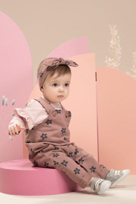 Mädchen trägt Flower Baumwolle Trägerhose Latzhose in Dunkelrosa - Stirnband mit Schleife in rotbraun rosa - LOVE Langarmshirt mit Rüschen hellrosa von Pinokio - Babyfoto sitzendes Kind