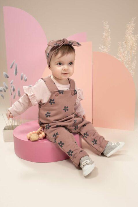 Mädchen trägt rotbraune Baby Flower Stirnband mit Schleife - Hellrosa Rüschen LOVE Oberteil langarm - Latzhose lang mit Blumen gemustert rosa von Pinokio - Kinderfoto lachendes Kind