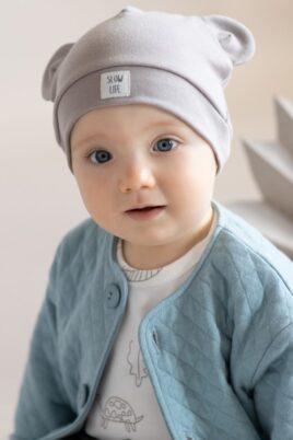 Junge trägt beige Babymütze mit Ohren & Patch SLOW LIFE - Basic Langarm Babybody weiß mit Tieren & Pflanzen OEKO TEX Baumwolle - Kinder Oberteil Sweatshirt mit Knöpfen gesteppt blau türkis von Pinokio - Babyfoto Nahaufnahme