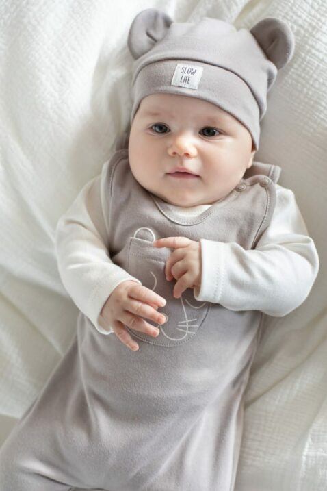 Junge trägt beige Babymütze mit Ohren & Patch SLOW Life aus OEKO TEX Baumwolle - Heller Tier Einteiler Strampler mit Fuß & Panther Tasche vorne von Pinokio - Babyfoto liegender Junge