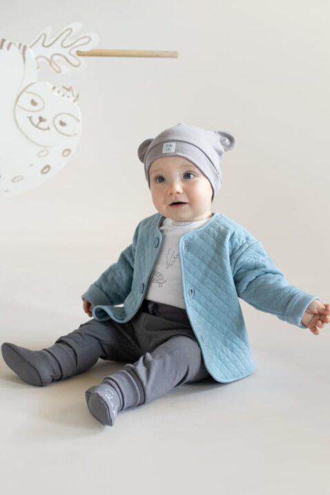 Junge trägt blaue Sweatjacke gesteppt - Beige Babymütze mit Ohren Patch - Weißen Body Langarm mit Tiere Affen Panther Schildkröten - Pumphose mit Taschen graphit grau & Patch von Pinokio - Babyfoto lachender Junge