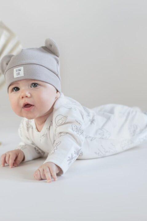 Junge trägt weißen Einteiler Schlafoverall Schlafanzug mit Füßen & Schildkröten, Affen, Panter Tiere aus OEKO TEX- Beige Baby Baumwollmütze mit Ohren & SLOW LIFE Patch von Pinokio - Babyfoto krabbelnder Junge