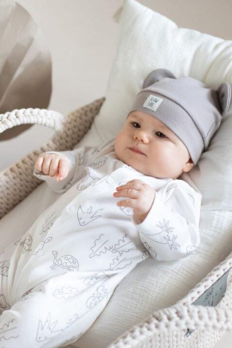 Junge trägt weißen Schlafanzug Schlafoverall mit Füßen & Panther, Affen, Schildkröten Tiermotive aus OEKO TEX Baumwolle - Kinder Mütze mit Ohren & Patch SLOW Life von Pinokio - Babyfoto Junge liegend