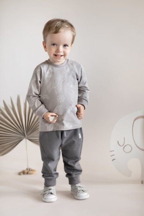Junge trägt beige Langarmshirt Sweatshirt mit Affen, Schildkröten, Turtles, Panther, Palmen OEKO TEX - dunkle graue Pumphose Haremshose mit Kordel & Patch SLOW LIFE Kinderhose von Pinokio - Babyfoto stehender Junge