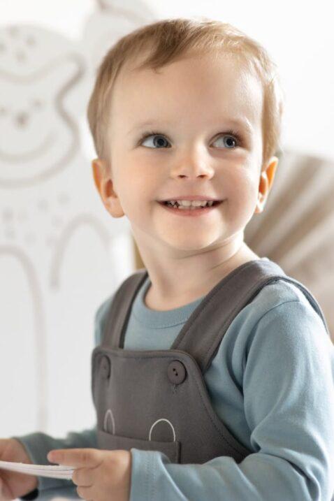Junge trägt graue grey dungarees Baby Latzhose Trägertasche mit Panther Tier Tasche - Kinder Body langarm mit Affe Baumwollbody OEKO TEX in Blau Türkis Blaugrün unifarben unisex von Pinokio - Babyfoto Nahaufnahme