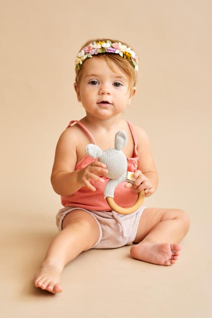 Sitzendes Mädchen spielt mit Babyspielzeug Holz Beißring & hellgraue Rassel Strick Hase Mila aus OEKO TEX Bio Baumwolle handgefertigt Motorikspielzeug von Knit A Buddy - Babyfoto Kinderfoto