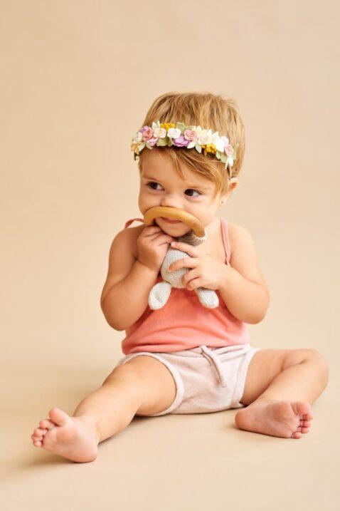 Sitzendes Mädchen mit Babyspielzeug Rassel Hase Kaninchen MILA Beißring aus Holz - Handmade & hochwertige OEKO TEX zertifizierte Pima Bio Baumwolle von Knit A Buddy - Kinderfoto Babyfoto