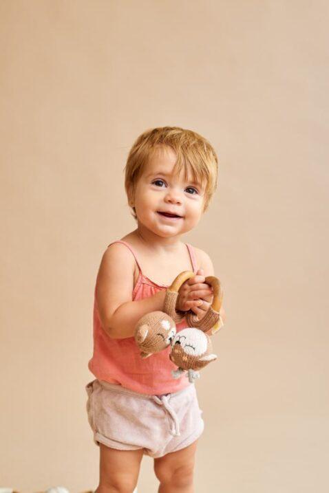 Lachendes Mädchen spielt mit Babyspielzeug Holz Beißring Rassel Strick Bär & Reh aus OEKO TEX Bio Baumwolle handgefertigt Motorikspielzeug von Knit A Buddy - Babyfoto Kinderfoto Set Bär & Rehkitz